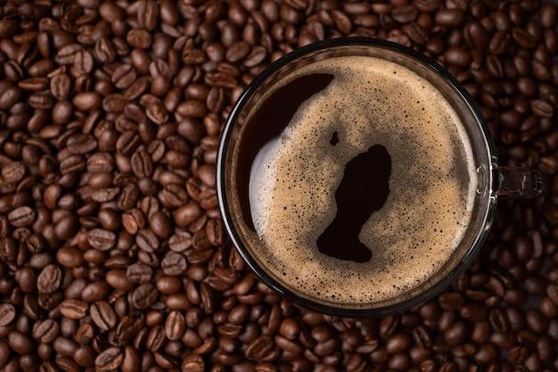 コーヒーカップとブラックコーヒー豆のグループの上面図が背景です。濃い黒のエスプレッソ、コーヒーの背景、テクスチャーの根拠
