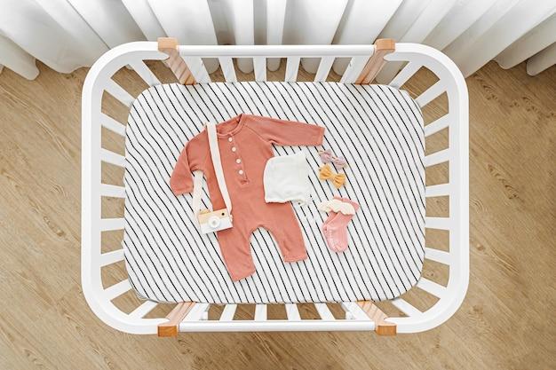 유아용 침대, 요람에 있는 아기 옷과 액세서리의 상위 뷰. 아기 방에 있는 신생아를 위한 나무 요람.