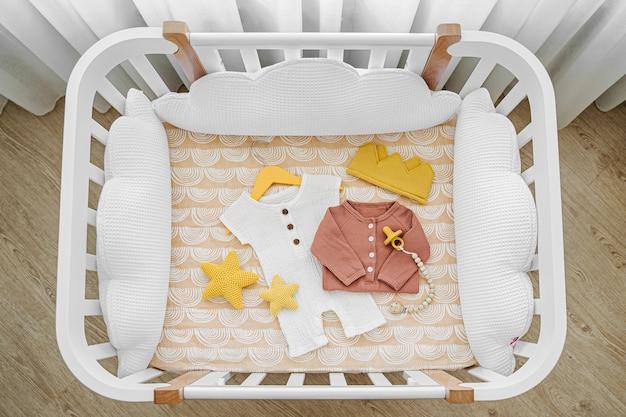 유아용 침대, 요람에 있는 아기 옷과 액세서리의 상위 뷰. 아기 방에 흰색 베개가 있는 신생아용 나무 요람.