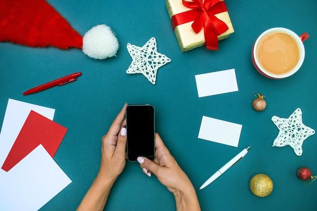 電話とクリスマスの装飾を持つ女性の手の平面図