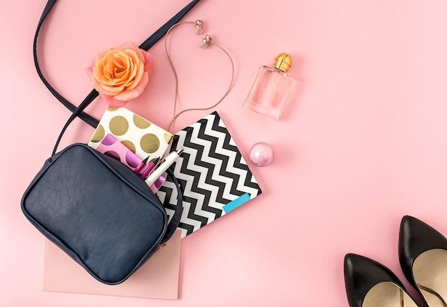 노트북, 펜, 연필, 헤드폰, 장미 배경에 장미가 있는 열린 여성 가방의 상단 보기