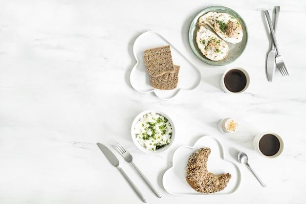 흰색 대리석 테이블에 슈퍼 푸드의 상위 뷰. 평평하다. 다양한 채소 재료와 채식주의자를위한 건강 식품. 아침 식사 테이블. 공간을 복사하십시오. 주형.
