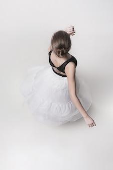 Вид сверху подростковой балерины на фоне белой студии