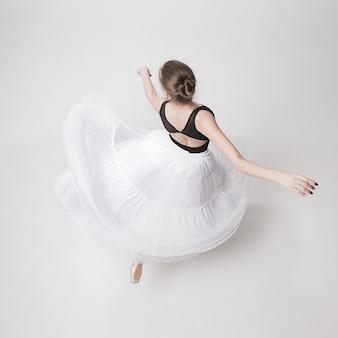 Вид сверху на балерину-подростка на белом