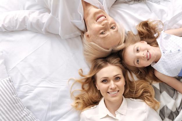 서로 다른 연령대의 세 여성이 머리를 맞대고 누워서 함께 즐기는 세 명의 행복한 쾌활한 얼굴의 상위 뷰