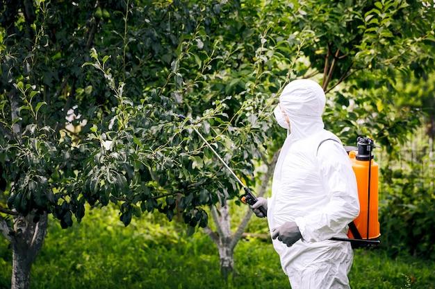 산업 농업의 주제. 한 사람이 농장에 독성 살충제나 살충제를 뿌립니다. 잡초 방제.
