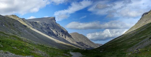 Вершины гор, хибины и пасмурное небо