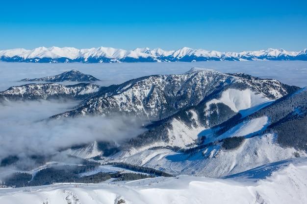 冬の山の頂上とスキーリゾートの谷の霧。晴天と青空。航空写真