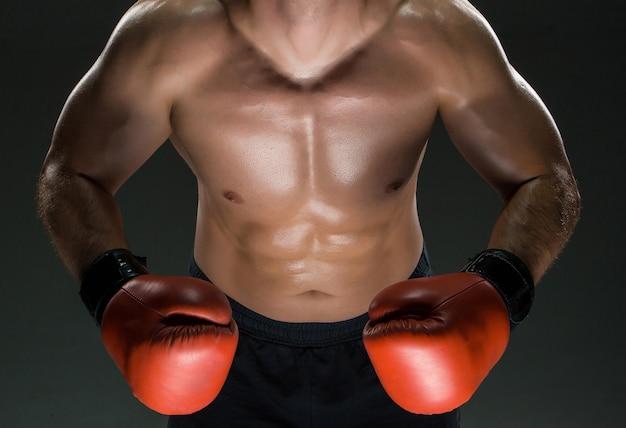 赤いボクシンググローブを身に着けている筋肉質の若い白人ボクサーの胴体
