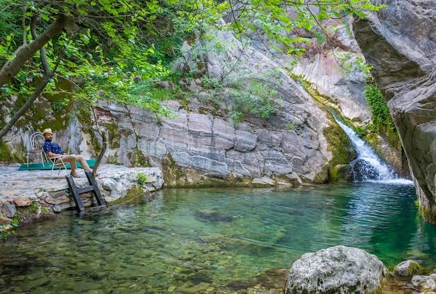 Турист наслаждается видом на небольшой живописный водопад
