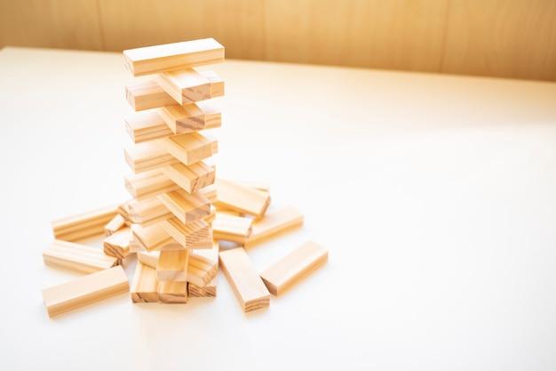 空を背景にした木のブロックのおもちゃからの塔のスタック。学習と能力開発の概念。