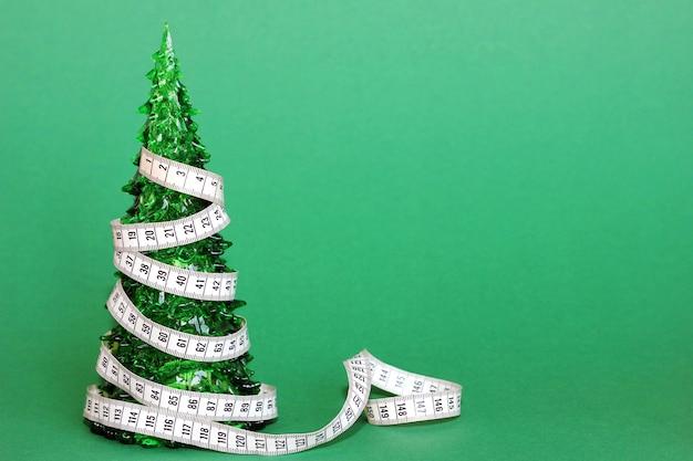 장난감 크리스마스 트리는 센티미터 테이프로 싸여 있습니다. 새해 휴일 개념 후 다이어트.