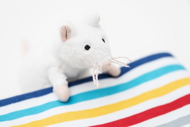 Игрушечная белая крыса выглядывает из-под одеяла.