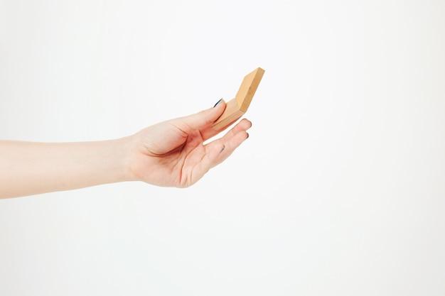 Игрушка деревянная головоломка в руке на белом фоне