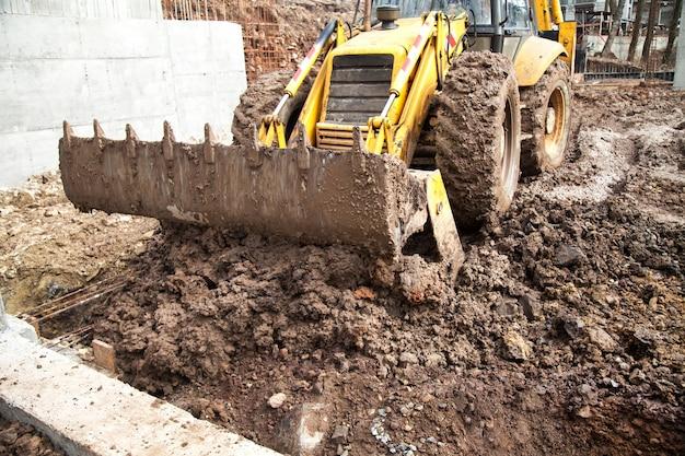 Трактор выравнивает участок под строительство.