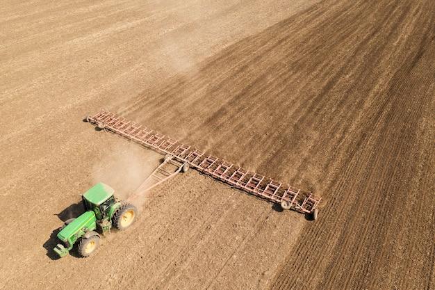 トラクターは土を耕します。春先の保湿に。航空写真。
