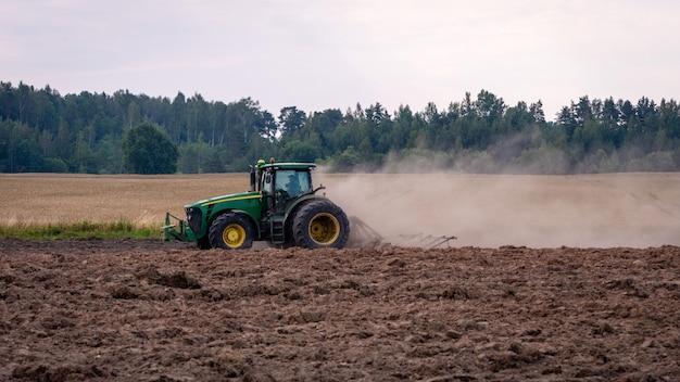 Трактор обрабатывает почву бороной.