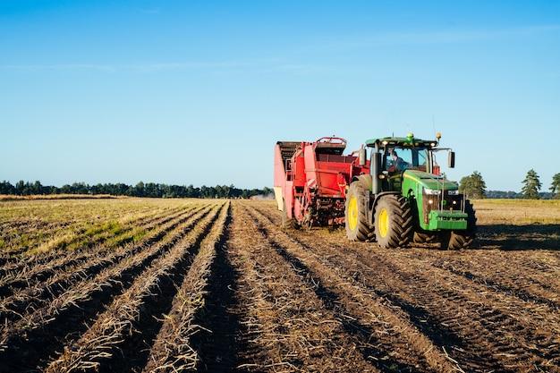 Трактор убирает картофель в поле. изображение сельскохозяйственной отрасли