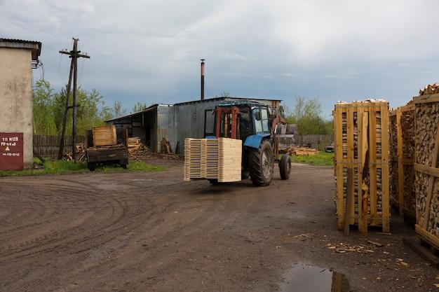 トラクターは、完成品の倉庫からトラックのコンテナにボードや材木を積み込みます。高品質の写真