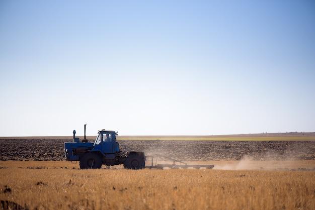 Трактор осенью пашет поле