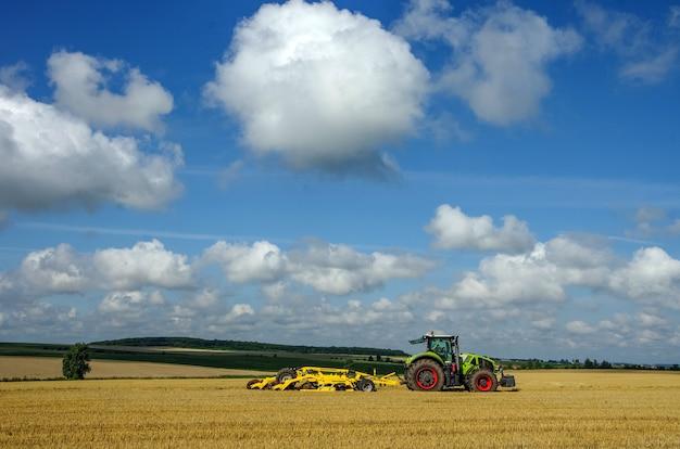 Трактор работает на поле под красивым небом с облаками, тянет за собой тяжелую борону - систему обработки почвы.