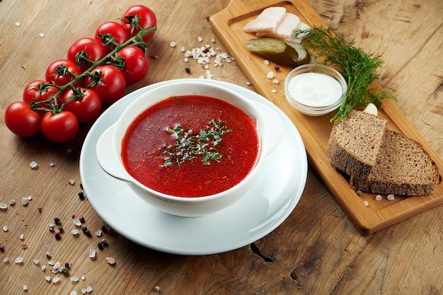 ウクライナ料理の伝統的な料理は、木製の表面に白い皿にボルシチ(赤いスープ)です。ボルシチベーコン、ブラウンパン、サワークリーム添え