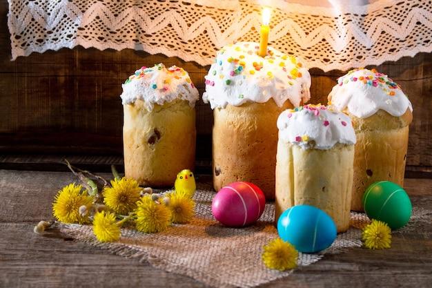 Традиционные пасхальные угощения: пирожные и красочные пасхальные яйца на столе в деревенском стиле. скопируйте пространство.