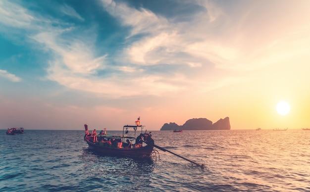 태국 왕국인 이국적인 피피섬 옆 바다에서 관광객들과 함께 하는 전통 어선. 숨막히는 화려한 일몰 배경입니다. 야생 자연의 아름다움입니다.