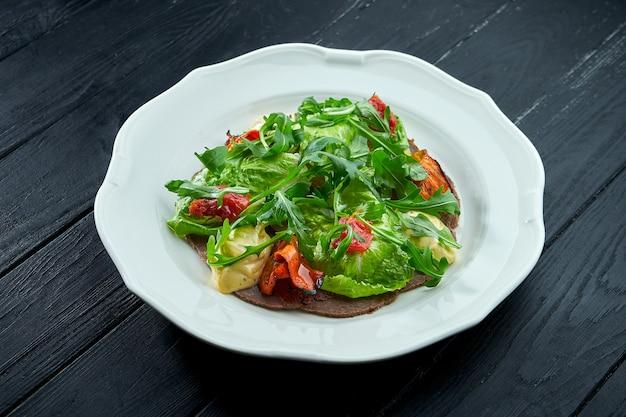 Традиционный итальянский салат-закуска - это вителло тоннато. тонко нарезанная говядина с рукколой, помидорами и соусом песто, подается в белой тарелке на темном фоне