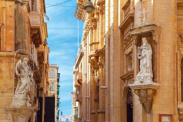 몰타의 수도인 발레타(valletta)에 있는 성자와 성모상으로 장식된 집의 모서리가 있는 전통적인 몰타 거리 계단