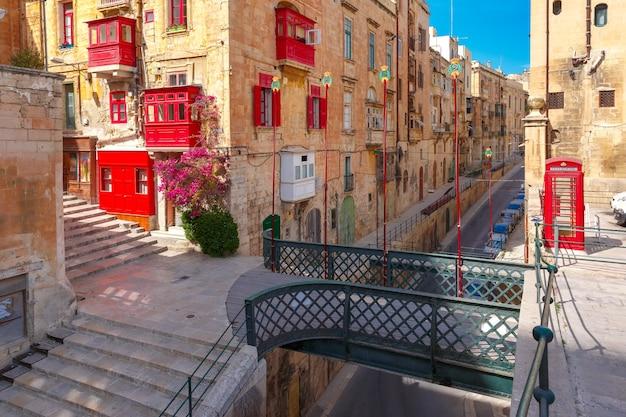 Традиционная мальтийская улица с красной телефонной будкой, ставнями и балконами в валлетте, столице мальты.