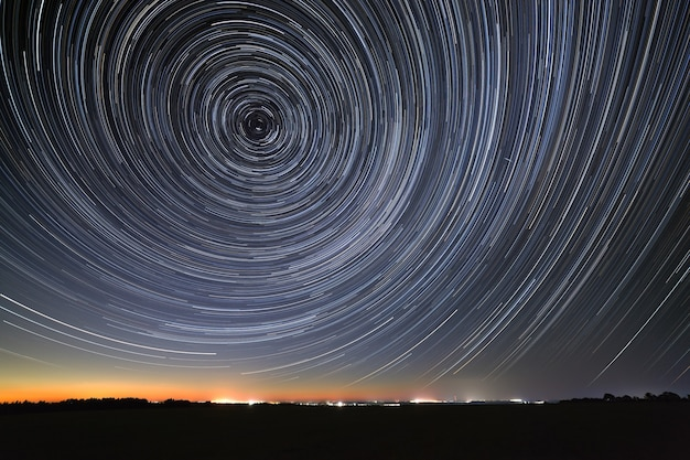 След звезд на ночном небе отражается в реке. движение в космосе сфотографировано на длинной выдержке.