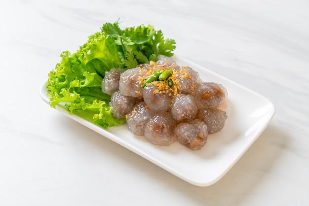 Прозрачные шарики называются саку сай му или шарик из вареных пельменей из тапиоки со свиной начинкой.