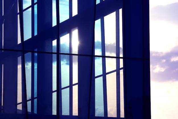 空と太陽に対する建物の透明なファサード