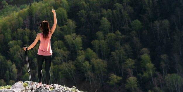 旅行者は喜んで山に登ります。山でのハイキング。マウンテンスポーツ。山の頂上にいる男。マウンテンツーリズム。山への旅。コピースペース