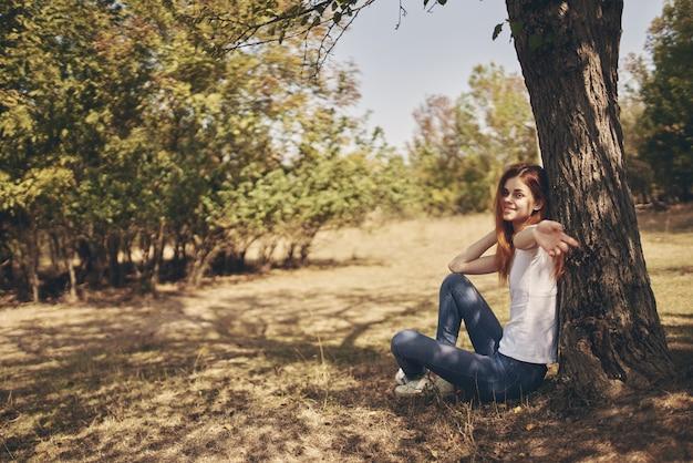 Путешественник сидит возле дерева на природе в лесу в джинсах и футболке.