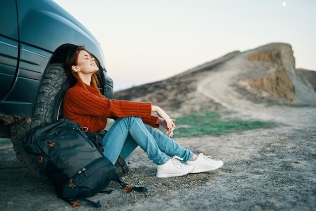 여행자는 산의 자연 속에서 차 근처에 앉아 있고 측면에는 배낭이 있습니다.