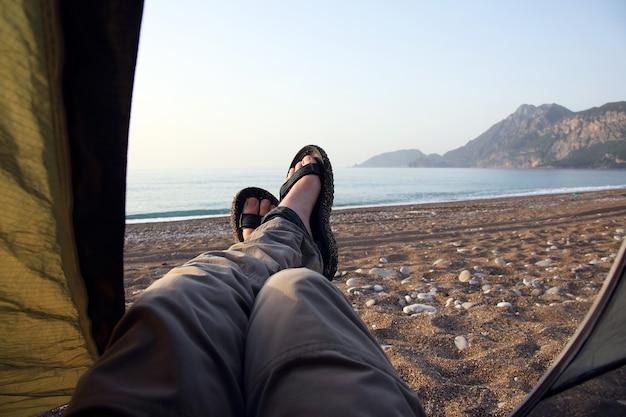여행자는 바다를 배경으로 텐트 밖으로 발을 내밀었다.