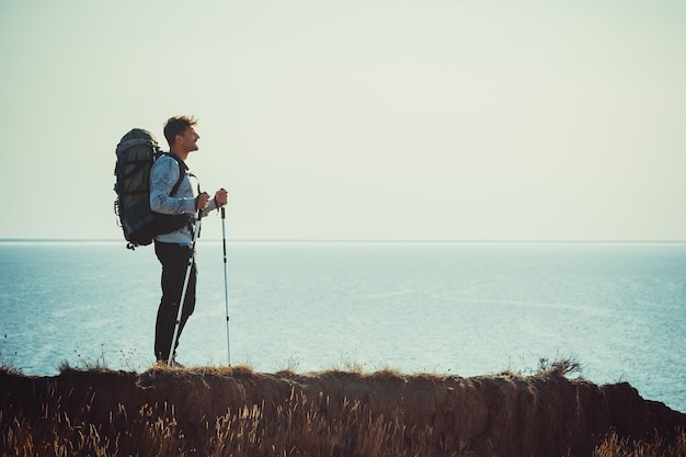 海の上の山の頂上に立っているバックパックを持つ旅行者