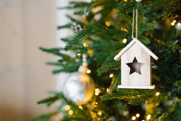 Елка украшена серебряным шаром и игрушечным деревянным домиком.