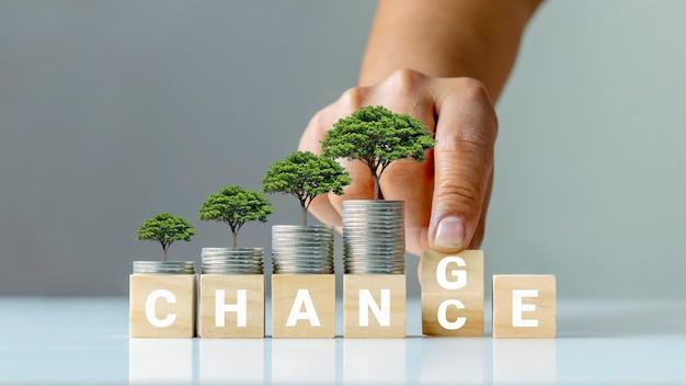 コインと手の上の木は、それを個人的な成長と経済成長の機会に変えることによって、木製の立方体をひっくり返します。