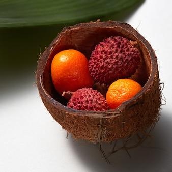 Тропические экзотические фрукты личи и кумкват в скорлупе кокоса с вечнозелеными листьями, изолированными на белом фоне. фото крупным планом.