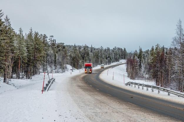 Грузовик едет по заснеженной арктической дороге.