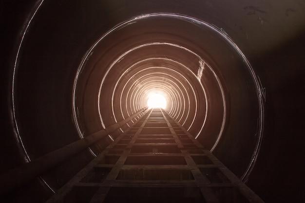 У большой стальной трубы туннеля есть черная тень и свет в конце туннеля.