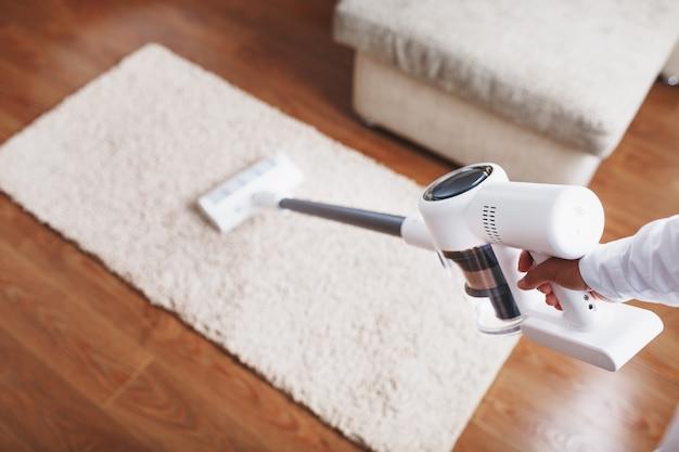 무선 청소기의 터보 브러시는 집에 있는 카펫을 클로즈업으로 청소합니다. 청소를 위한 현대 기술.