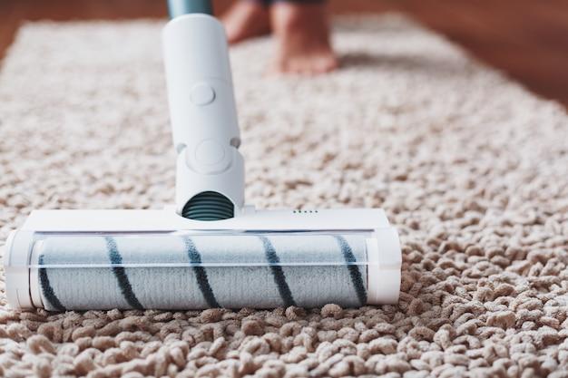 무선 청소기의 터보 브러시는 집에 있는 카펫을 클로즈업으로 청소합니다.