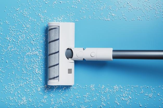진공 청소기의 터보 브러시는 파란색 배경에 있는 흰색 공을 청소합니다. 청결과 청소의 개념입니다. 평면도
