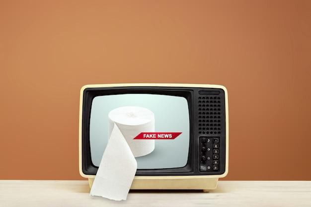 テレビはテーブルの上にあり、トイレットペーパーを放送しています。フェイクニュース、イエロープレス、フェイクニュースのコンセプト。