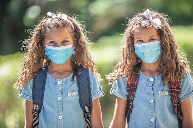 마스크를 쓴 쌍둥이 자매가 코로나19 격리 기간 동안 학교로 돌아갑니다.