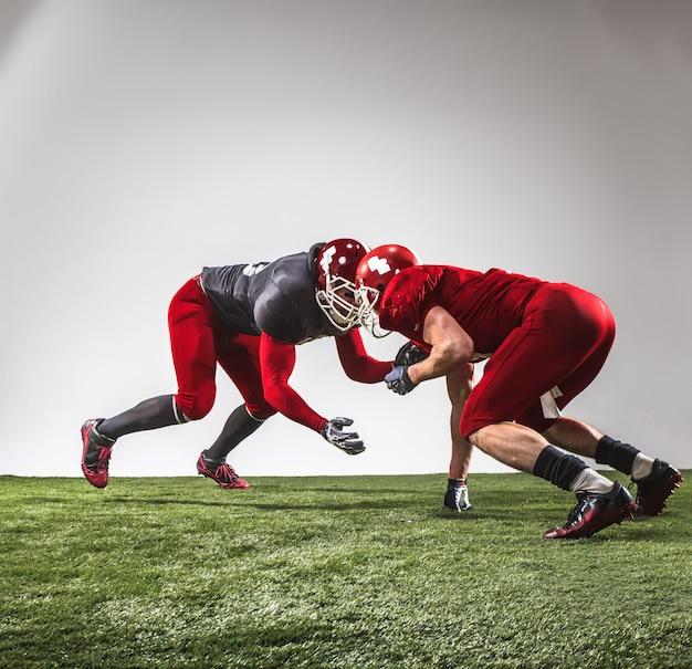 Два игрока в американский футбол в действии на зеленой траве и сером фоне.
